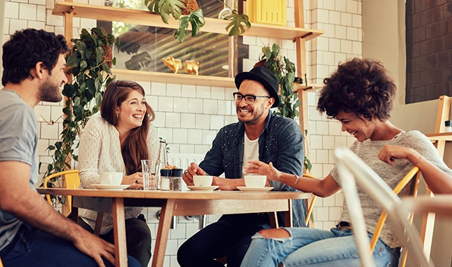 group of people sitting at table drinking coffee and laughing