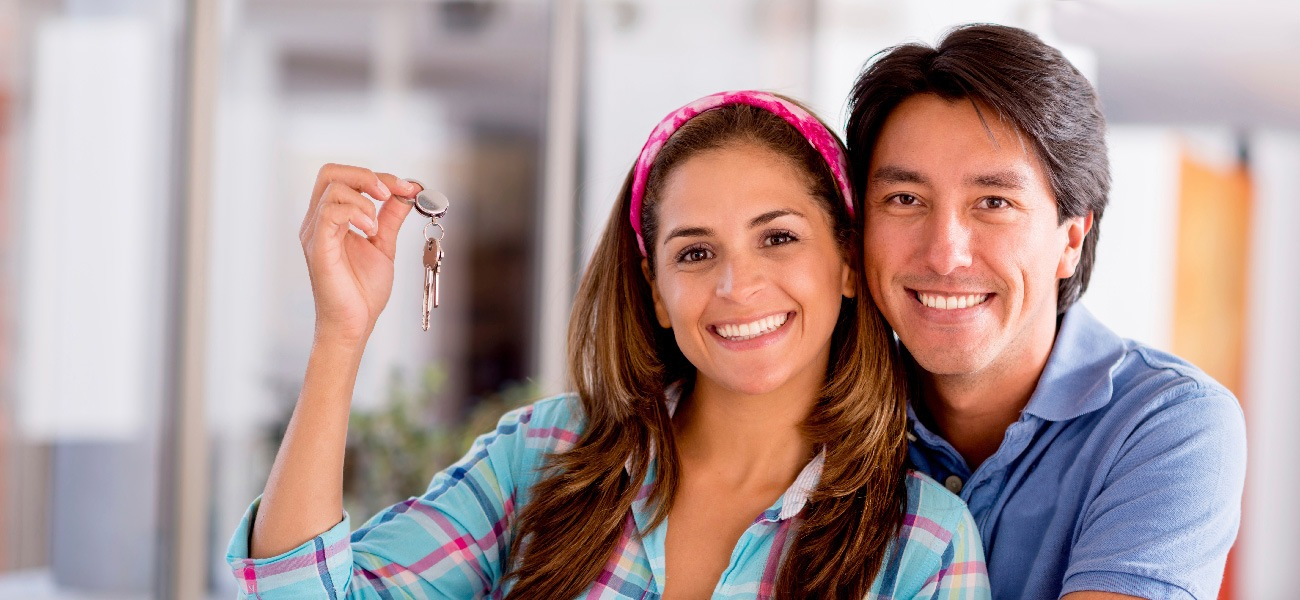 young couple smiling and holding keys