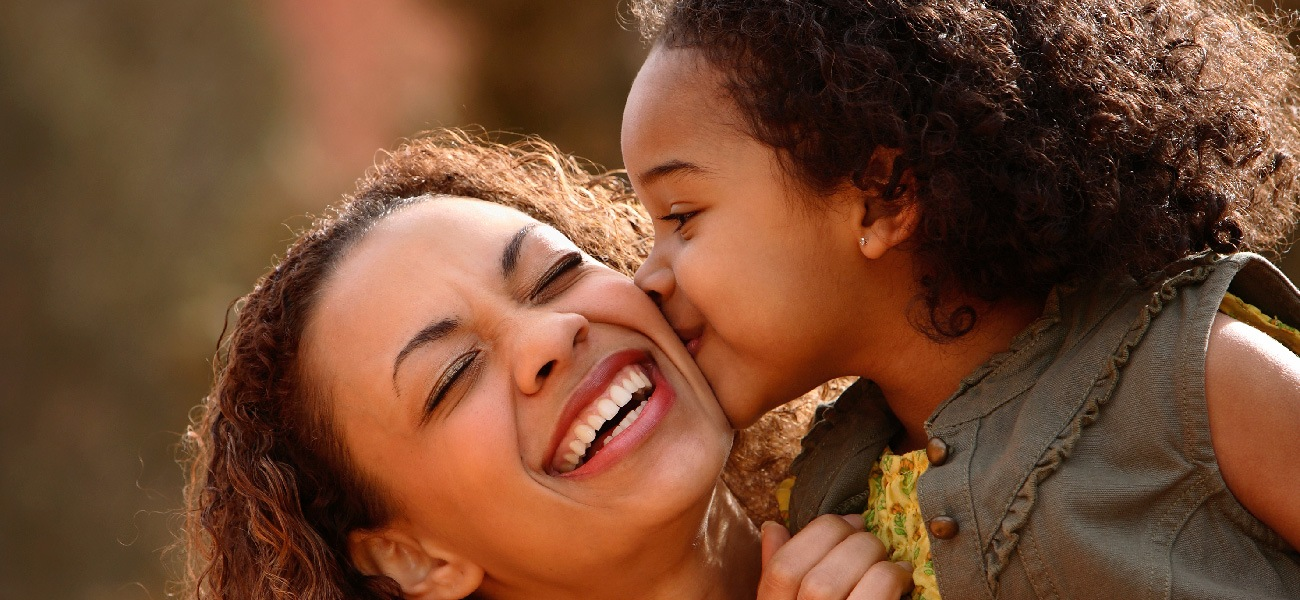 young child kissing mom's cheek